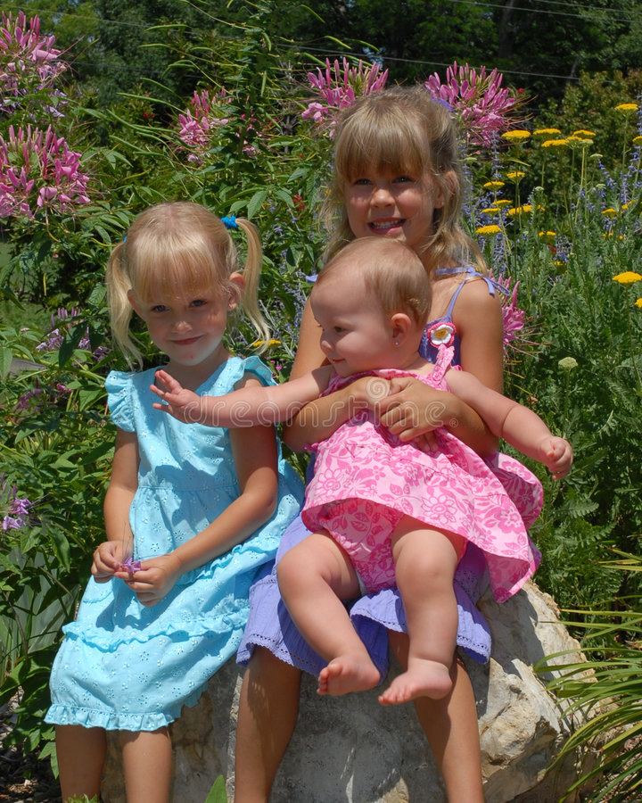 Girls posing in flower garden. Portrait of three small girls in pretty dresses, posing in a flower garden stock images