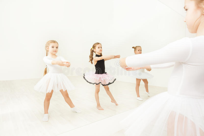 Girls practicing near the mirror in ballet studio royalty free stock images