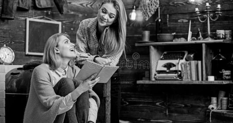 Girls reading together, family leisure activity. Teenager studying literature with her mom, home education concept. Mother and daughter looking at each other stock photography