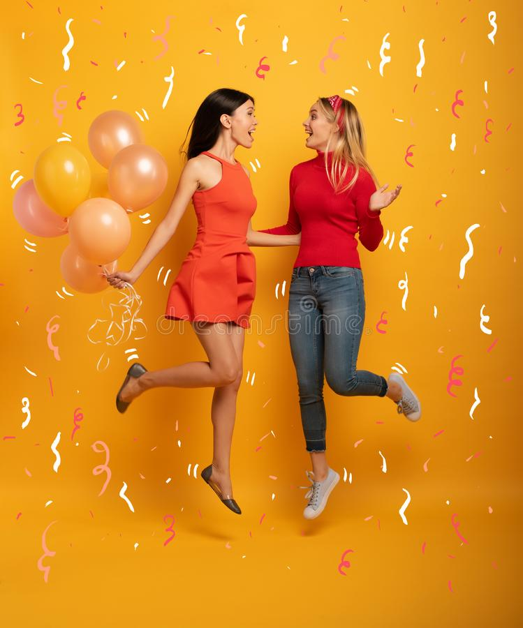Girls ready for a party with balloons. Joyful an happiness expression. Yellow background. Brunette and blonde girls are ready for a party with balloons. Joyful stock image