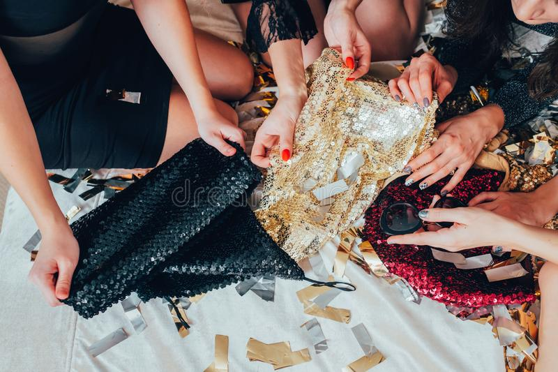 Girls relaxation glamor lifestyle sequin outfit. Girls relaxation . Glamor look and lifestyle trends. Women in black choosing sequin outfit. Urban fashion stock photo