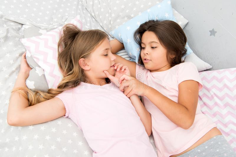 Girls relaxing on bed. Slumber party concept. Girls just want to have fun. Invite friend for sleepover. Best friends. Forever. Consider theme slumber party stock photo