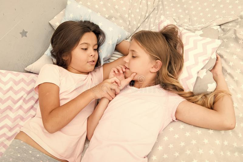 Girls relaxing on bed. Slumber party concept. Girls just want to have fun. Invite friend for sleepover. Best friends. Forever. Consider theme slumber party royalty free stock photo