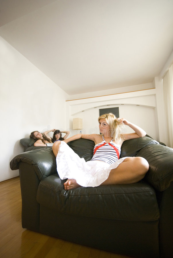 Girls relaxing in living room. Three girls relaxing in the living room stock photo