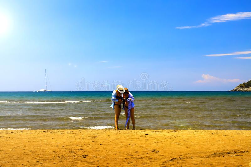 2 girls are reviewing newly taken photos on the picturesque coast, Turkey. 2 girls are reviewing newly taken photos on the picturesque coast of the Aegean Sea royalty free stock photos