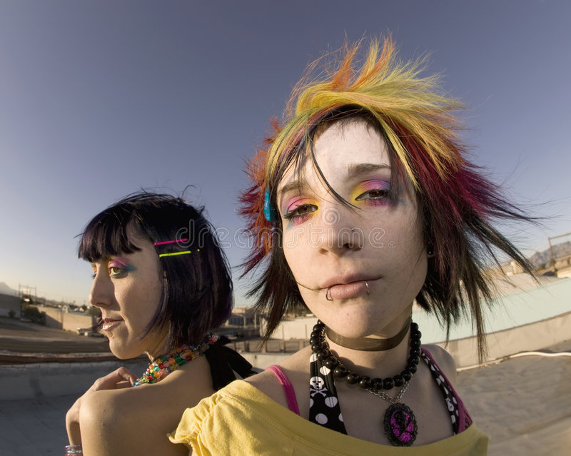 Girls on the Roof. Fisheye shot of girls in brightly colored clothing on a roof royalty free stock photos