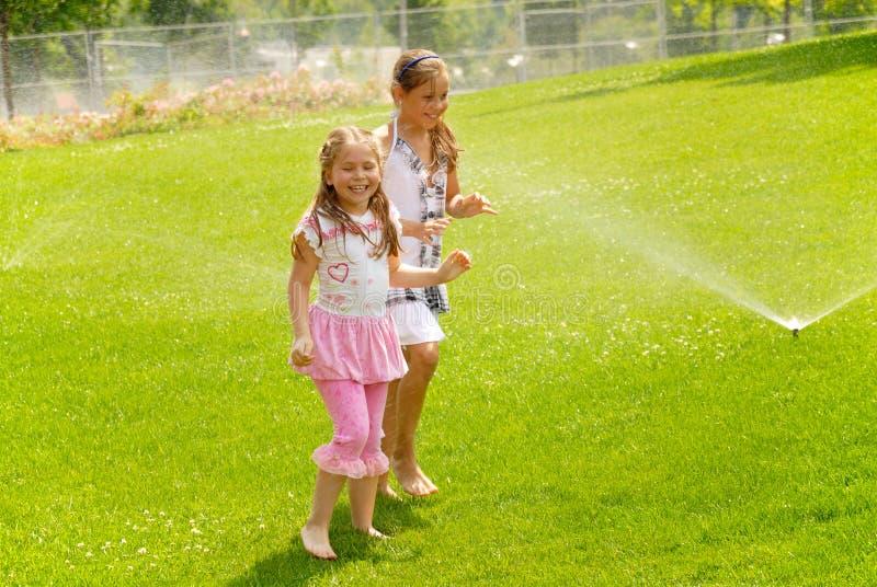 Download Girls Run Barefoot On A Grass Under Splashes Stock Photo - Image: 25535050