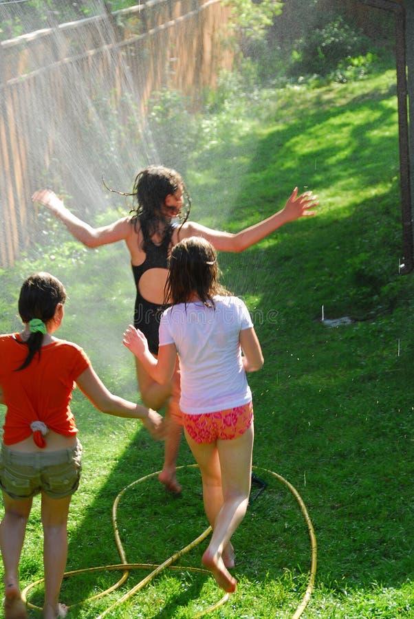 Girls run sprinkler stock photo