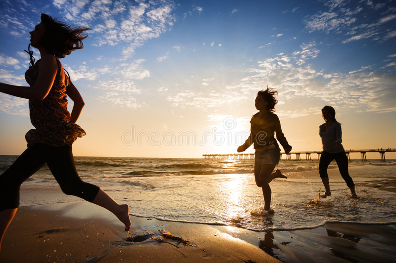 Girls running. Three girls at the beach running by the ocean at sunset royalty free stock photos