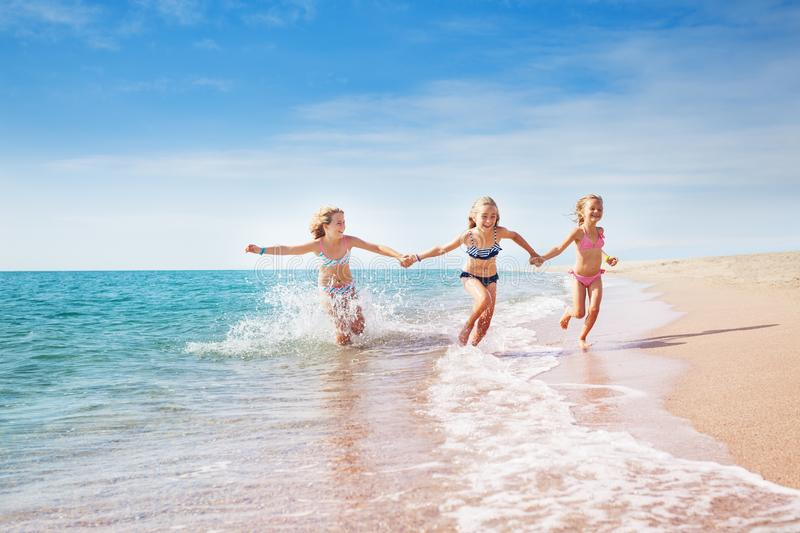 Girls running in sand and waves of sunny beach royalty free stock photo