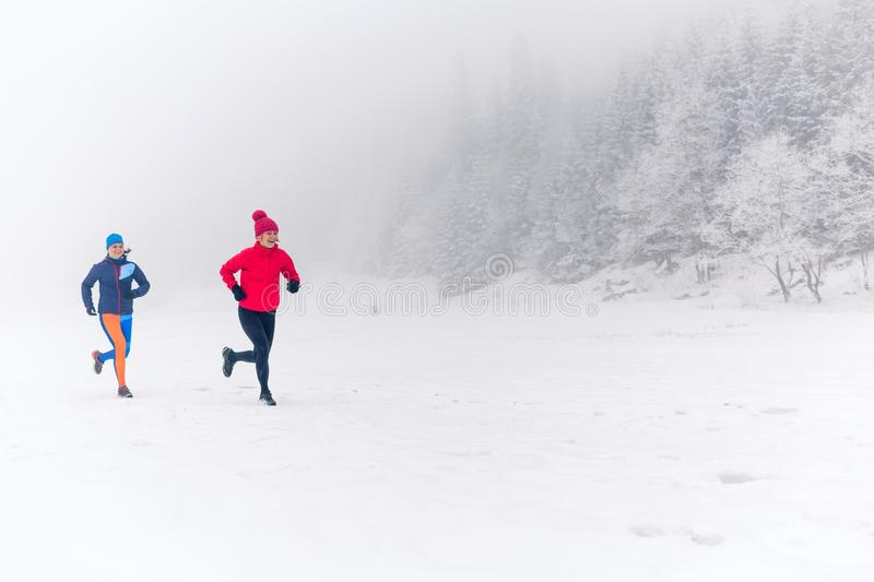 Two women trail running on snow in winter mountains stock images