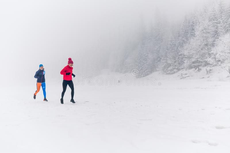 Girls running together on snow in winter mountains. Sport, fitness inspiration and motivation. Two women partners trail running in stock photography