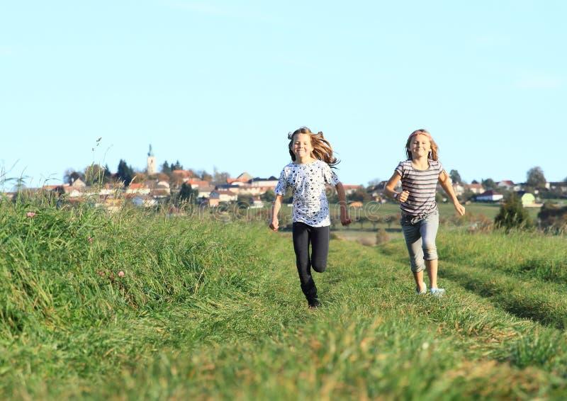 Girls running from village royalty free stock image