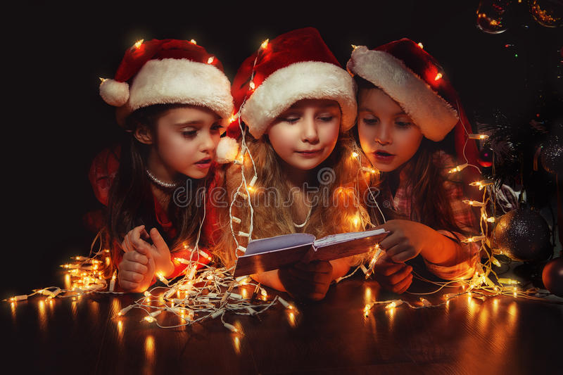 Girls in Santa hats have a Christmas. Happy small three girls in Santa hats have a Christmas stock photo