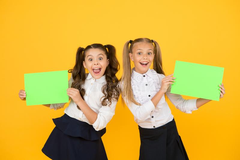 Girls school uniform hold poster. School girls show poster. Social poster copy space. Socialization involves how. Children get along with each other. Visual royalty free stock photography