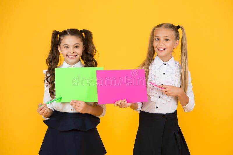 Girls school uniform hold poster. Visual communication concept. School friendship. School girls show poster. Presentation poster copy space. Children stock photo