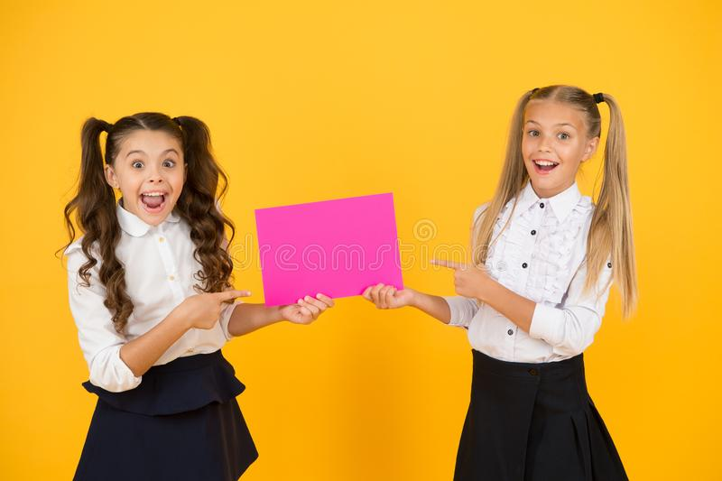 Girls school uniform hold poster. Visual communication concept. School friendship. School girls show poster. Social. Poster copy space. Socialization involves royalty free stock photography