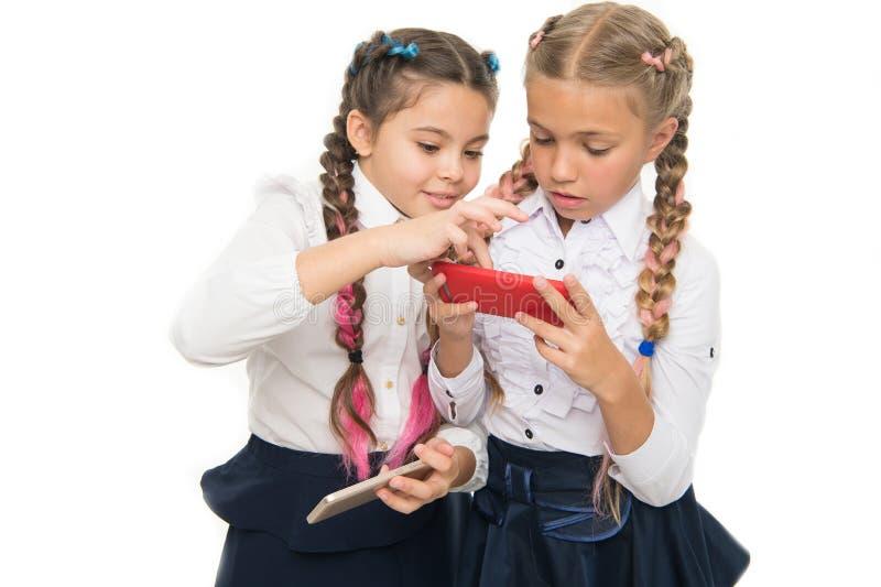 Girls school uniform surfing internet. Modern life. Schoolgirls use mobile internet smartphone. School application. Smartphone. Mobile addiction. Worldwide net royalty free stock photo