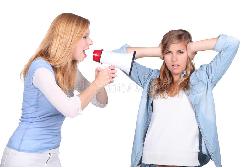 Girls screaming in a bullhorn. And girl covering her ears royalty free stock photos