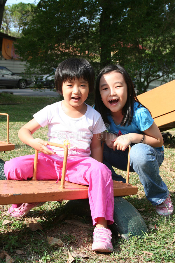 Girls on seesaw royalty free stock photography