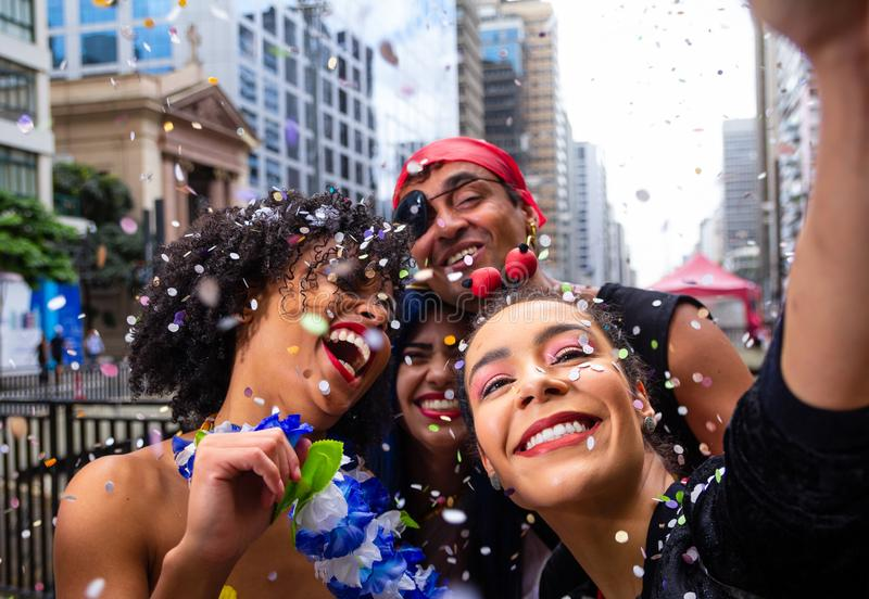 Girls selfie at street party parade, brazilian carnaval. Group of Brazilian friends in costume celebrating. Girls taking selfie at street party parade, brazilian royalty free stock photography