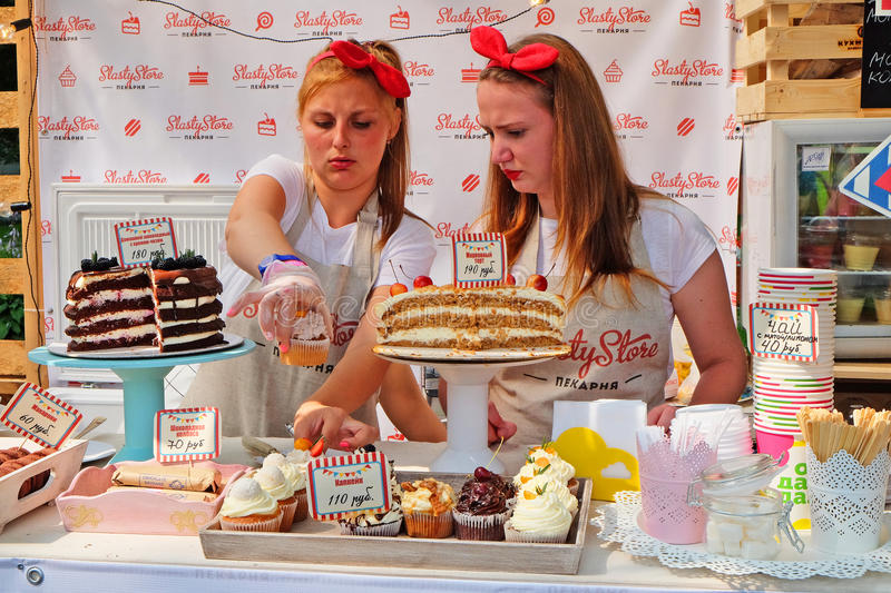 girls sellers are standing at a counter with fresh pastries stock image