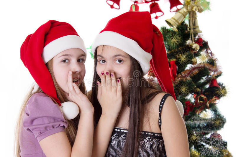 Girls sharing each other secrets on Christmas Eve stock photography