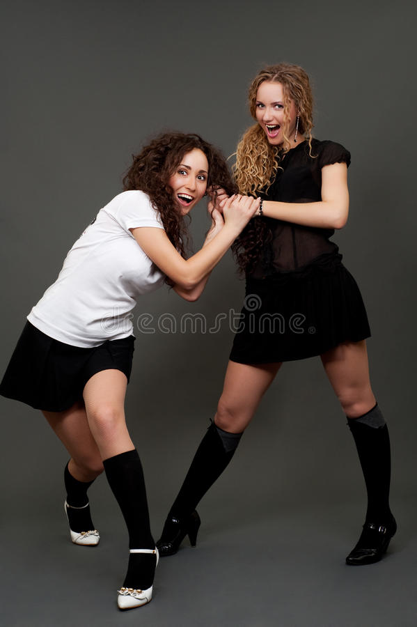Girls in short skirts having quarrel stock image