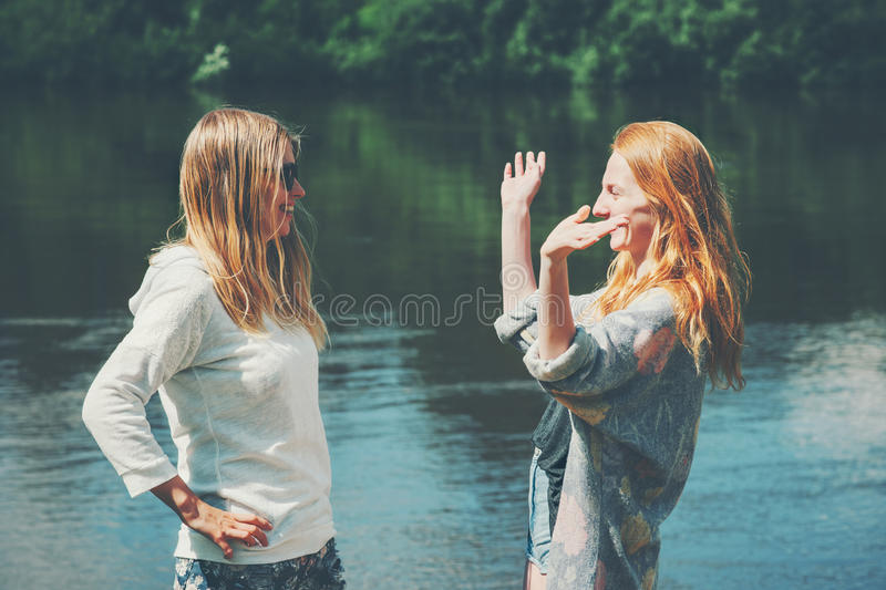 Girls sisters couple traveling together walking at lake stock images