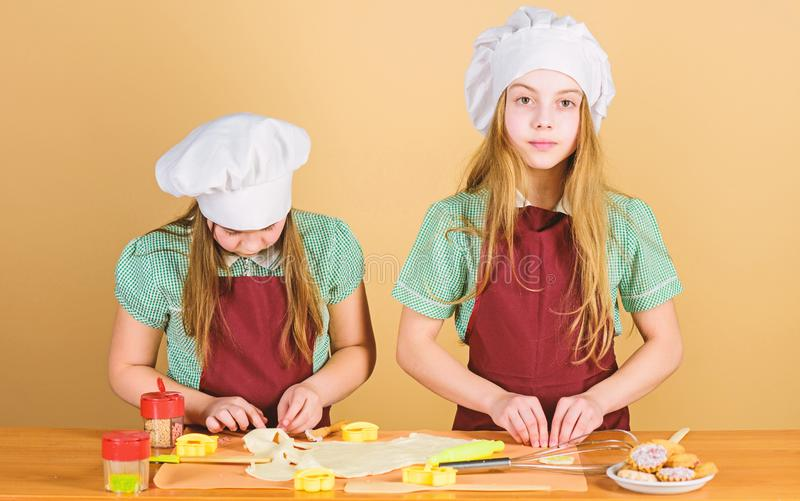 Girls sisters having fun ginger dough. Homemade cookies best. Kids baking cookies together. Kids aprons and chef hats. Cooking. Family recipe. Culinary royalty free stock photos