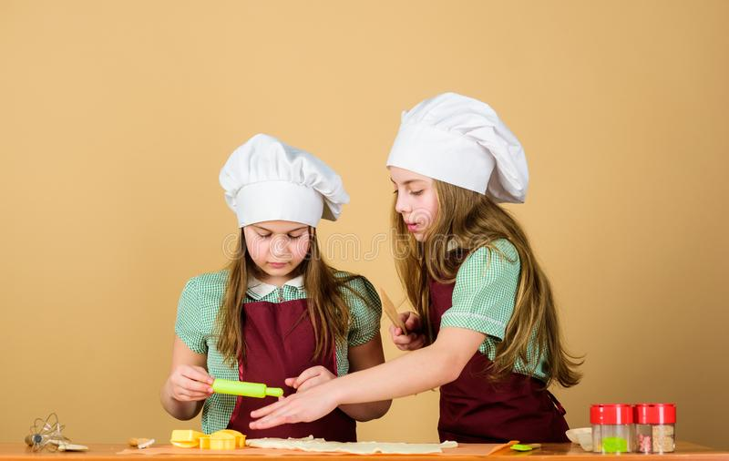 Girls sisters having fun ginger dough. Kids baking cookies together. Kids aprons and chef hats cooking. Homemade cookies. Best. Family recipe. Cooking skill royalty free stock photos
