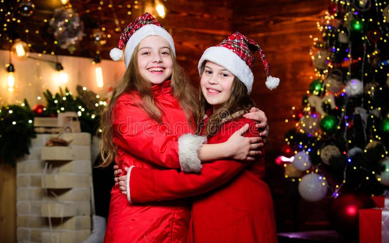 Girls sisters santa claus costumes. Kids lovely friends meet Christmas holiday. Joy and Noel. Family celebrate Christmas royalty free stock images