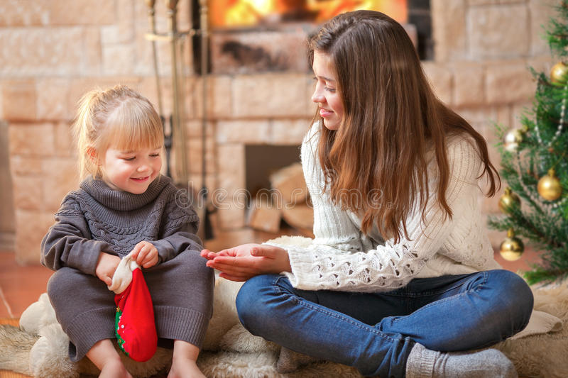 Download Girls Sitting Fireside Opening Christmas Presents Stock Image - Image: 26478799