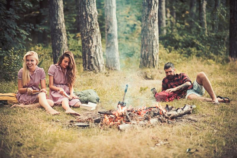 Girls sitting next to campfire while reading books. Bearded guy lying on grass in forest. Friends camping in summertime royalty free stock photo