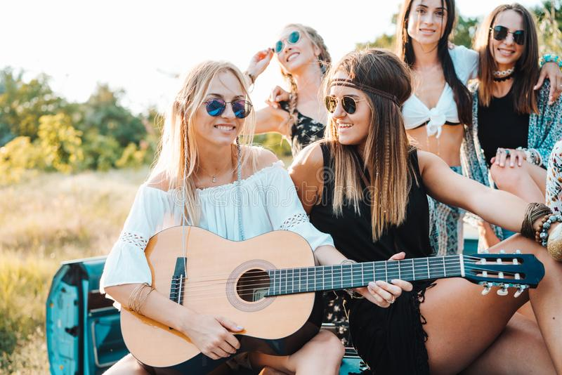 girls are sitting on the trunk with a guitar stock photo image of