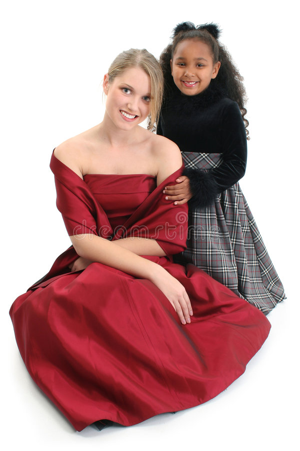 Girls smiling. Beautiful girl in red dress and cute little African American girl smiling and posing isolated over white background royalty free stock photography