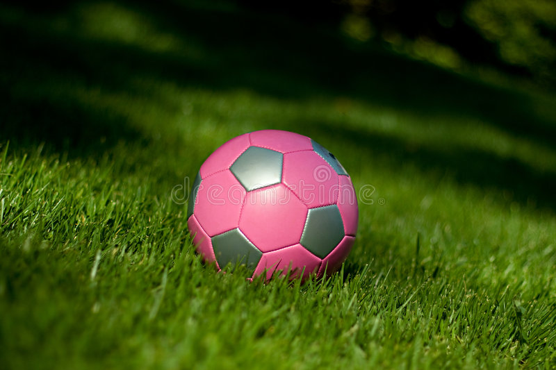 Girls' soccer ball in grass royalty free stock photography
