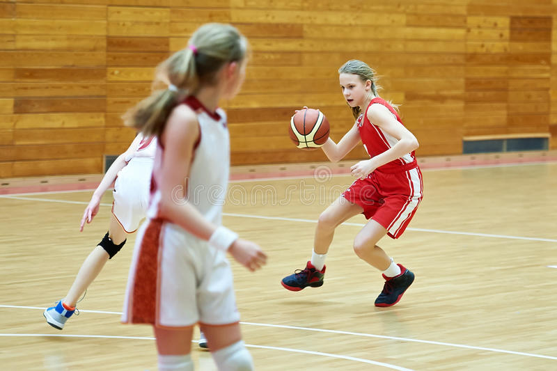 Girls in sport uniform playing basketball indoors. Girls athlete in sport uniform playing basketball indoors royalty free stock photo