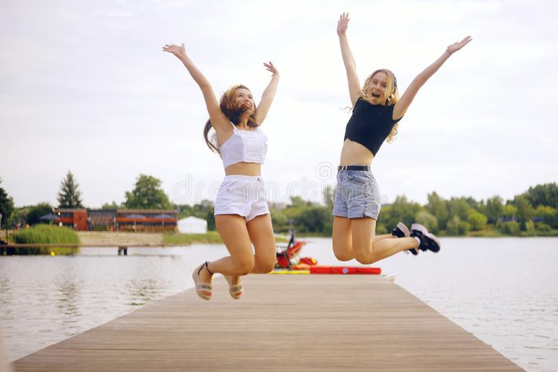 Girls stand on the pier near the river, lake, beach. Girls jump, raise their hands up, happiness, joy. Summer vacations, royalty free stock image