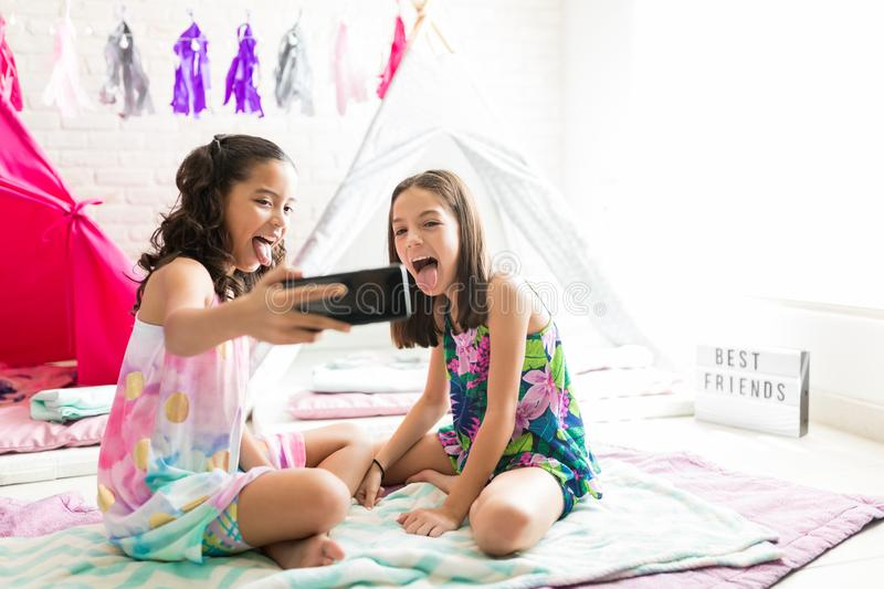Girls Sticking Out Tongue While Taking Selfie On Smartphone. Mischievous girls sticking out tongue while taking selfie on smartphone during pajama party at home stock photos