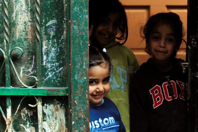 Girls in the street of Ramallah. Girl watch at photographer through door in refugee camp Aida, Ramallah, Palestine royalty free stock photography
