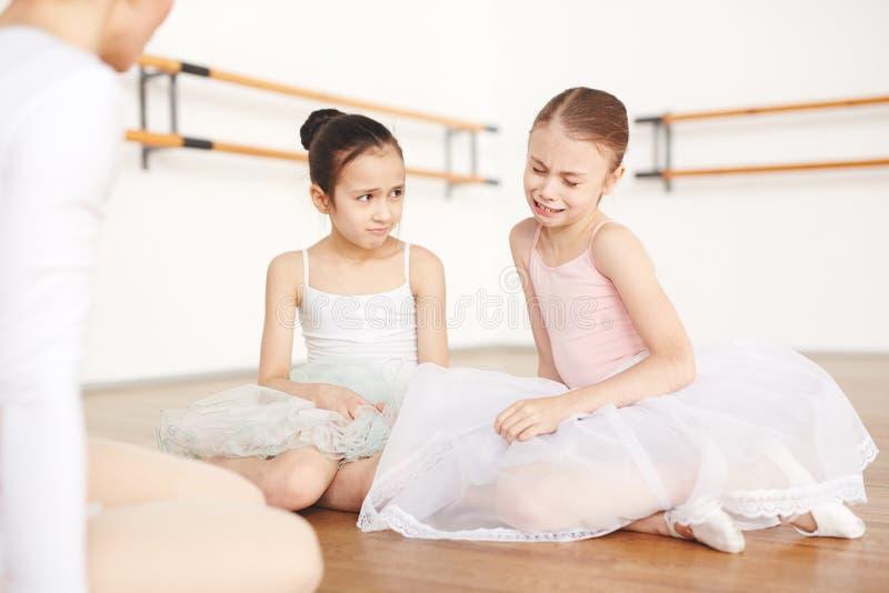 Little sad ballerinas sitting on floor in studio stock photography
