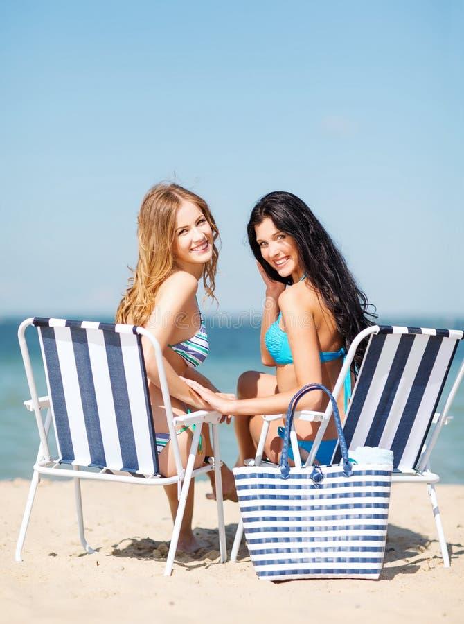 Girls sunbathing on the beach chairs. Summer holidays and vacation - girls in bikinis sunbathing on the beach chairs royalty free stock image