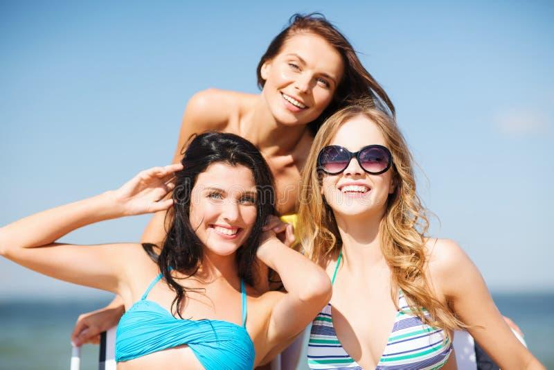 Girls sunbathing on the beach chairs. Summer holidays and vacation - girls in bikinis sunbathing on the beach chairs stock images