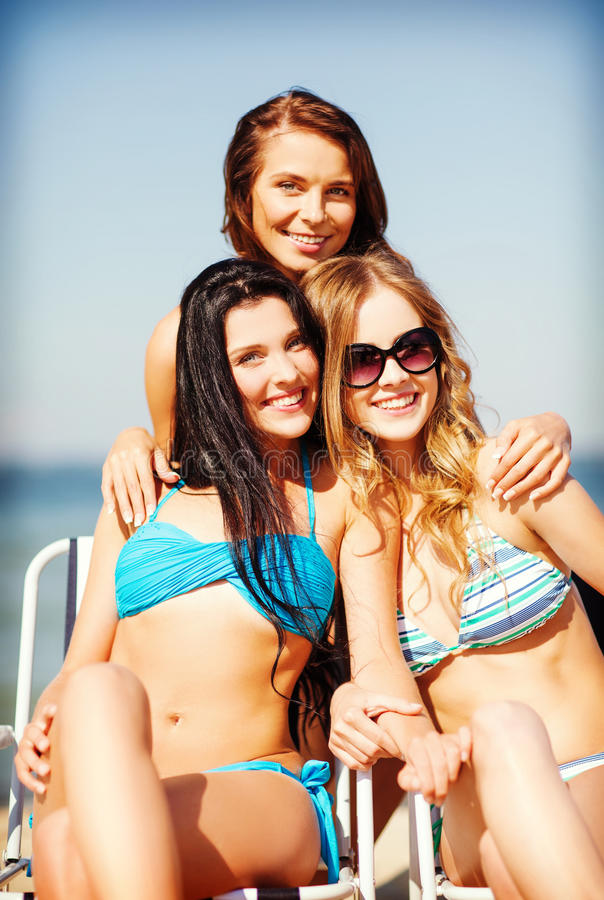 Girls sunbathing on the beach chairs. Summer holidays and vacation - girls in bikinis sunbathing on the beach chairs stock photos