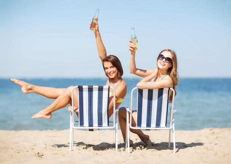 Girls sunbathing on the beach chairs. Summer holidays and vacation - girls sunbathing and drinking on the beach chairs stock photos