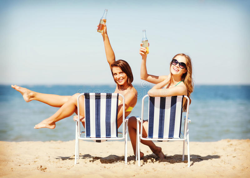 Girls sunbathing on the beach chairs. Summer holidays and vacation - girls sunbathing and drinking on the beach chairs royalty free stock photo