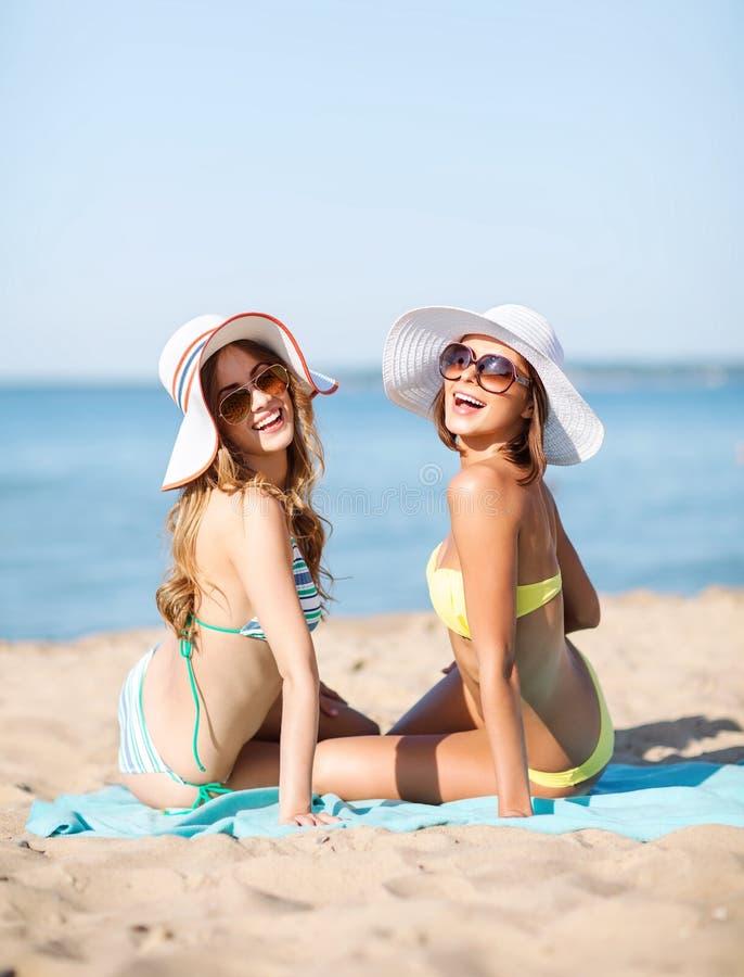 Girls sunbathing on the beach. Summer holidays and vacation - girls sunbathing on the beach stock image