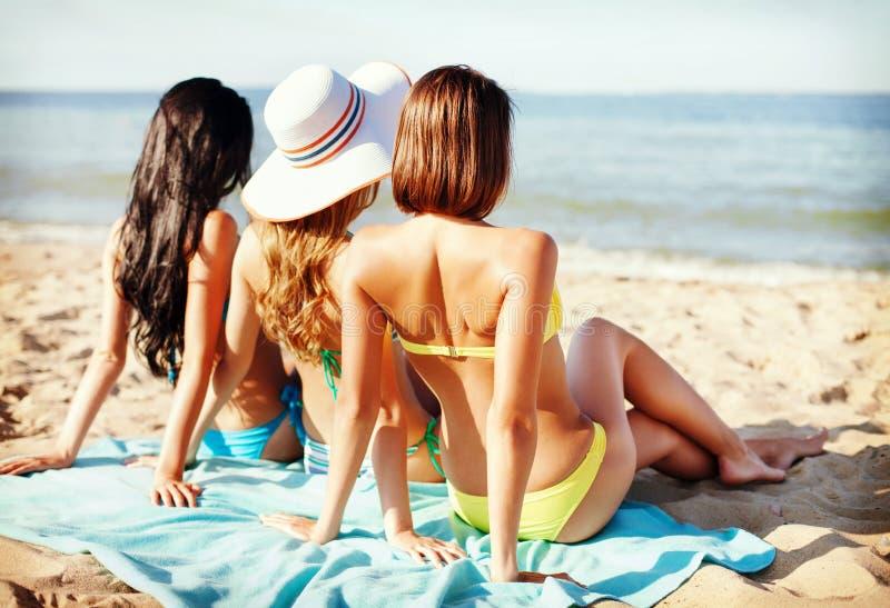 Girls sunbathing on the beach. Summer holidays and vacation - girls sunbathing on the beach royalty free stock images