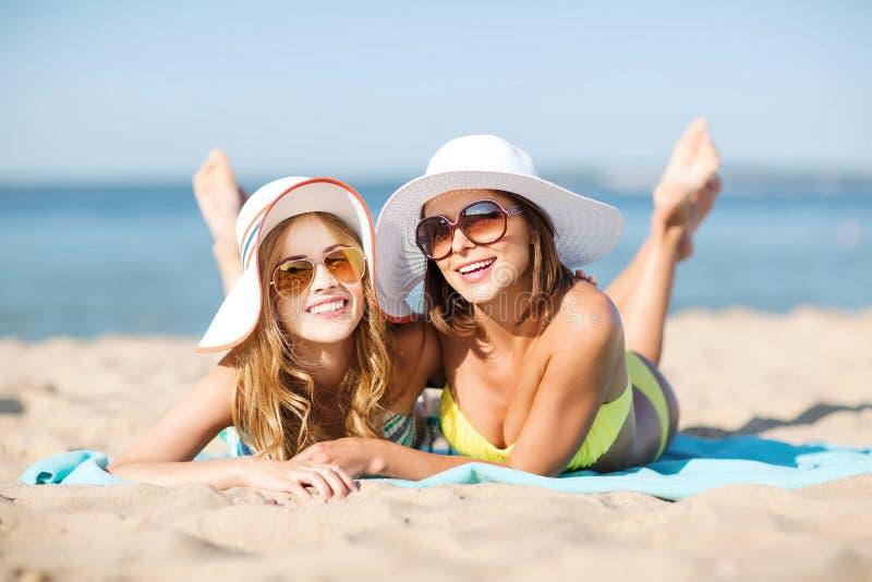 Girls sunbathing on the beach. Summer holidays and vacation - girls in bikinis sunbathing on the beach royalty free stock photography